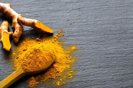 Fresh root and turmeric powder, indian spice, healthy seasoning ingredient for vegan cuisine Stock Photo
