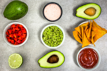 Traditional mexican food - guacamole with avocado and tortilla chips on table, party food for sharing