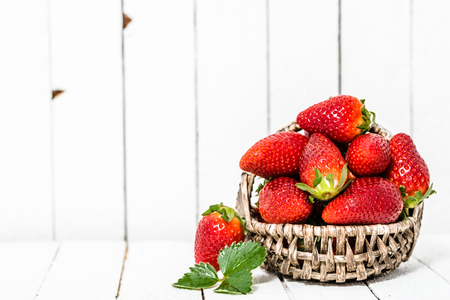 Organic strawberries on white wooden background. Red berries on table.