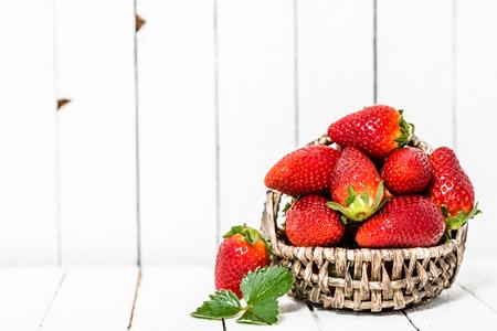 Fraises biologiques sur fond en bois blanc. Fruits rouges sur table.