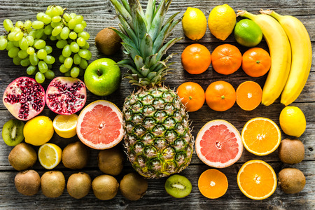 Table with fruit, tropical variety of assorted fruits on wood, healthy food and clean eating concept Stock Photo