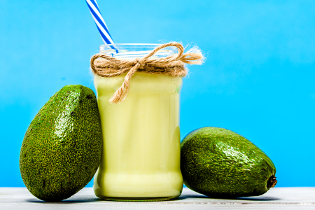 Jar of smoothie with avocado, healthy detox drink on blue background