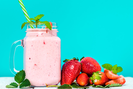 Strawberry smoothie in jar on table and fresh strawberries, healthy breakfast concept