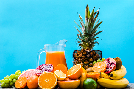 Fresh juice from fruits. Healthy juicy vitamin drink, refreshing summer beverage and tropical fruits on blue background.