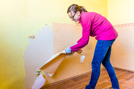 Woman renovating own home, flat wall repairing, removal old wallpaper