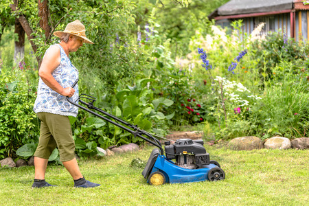 Woman gardener working in the garden, cutting grass with a mower, summer gardening