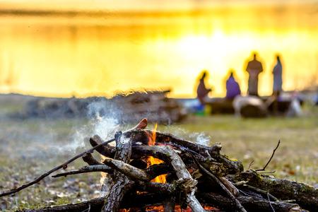 キャンプファイヤーとソーセージが火と煙の上で焼くキャンプ中の友人のグループ