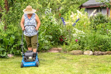 Senior woman working in the garden, cutting grass with a mower, autumn gardening