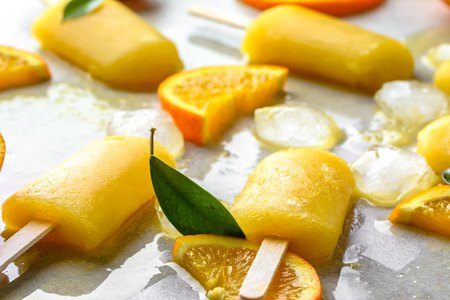 Orange popsicle with fresh oranges and ice, summer refreshing concept Stock Photo