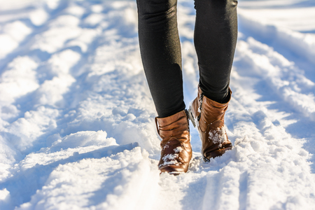 Woman walking in snow boots, winter womens shoes on the feet and legs dressed in leggings Stockfoto