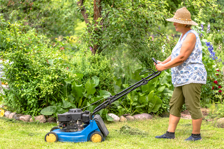 Woman gardener working in the garden, cutting grass with a mower. Lawn mowing in the summer garden.