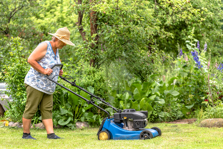 Woman working in the garden. Mowing grass with a mower. Gardener cuts the lawn in the garden at summer.