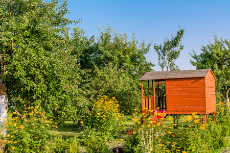 Summer kids house in green garden with flowers, playhouse cottage for children's play Stockfoto