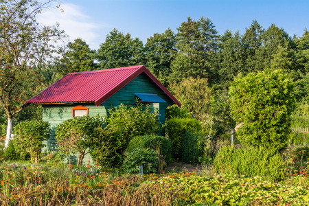 Wooden cottage in the garden in the summer countryside landscape