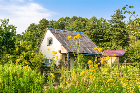 Rural house. Summer cottage with flowers in the garden, country landscape Stock Photo