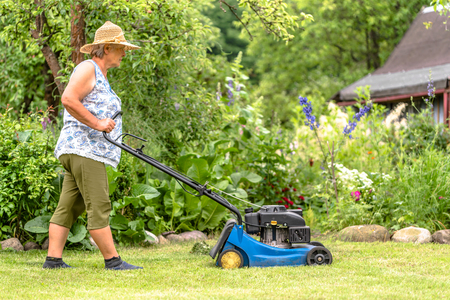 Gardener in the summer garden. Working woman with a mower during grass mowing. Stock Photo