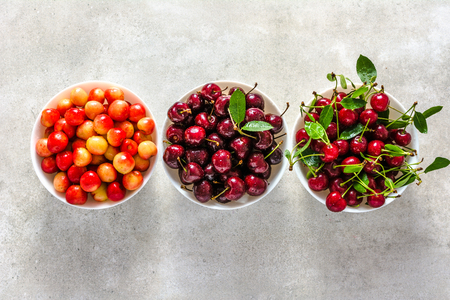 Various cherries, fresh fruit on plate on white background, ripe cherry, sweet fruit, top view Stock Photo