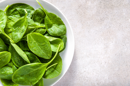 Green vegetables - spinach on plate, healthy food, vegan diet concept.