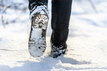 Female feet in boots in snow walking in winter Archivio Fotografico - 105586818