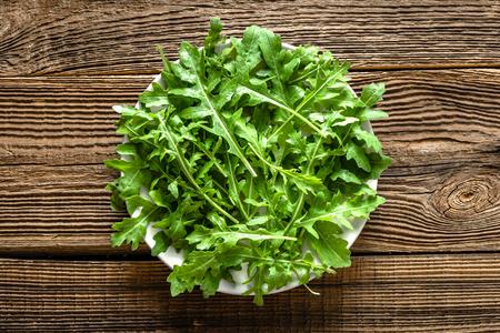 Green vegetables. Fresh arugula leaves on plate, healthy diet, vegetarian food concept