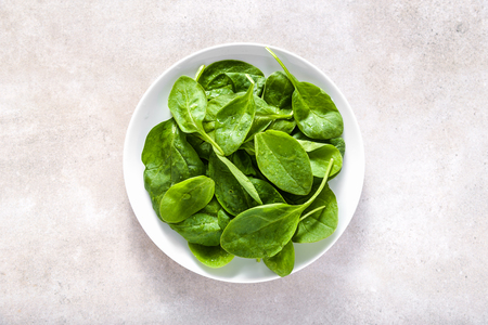 Fresh spinach. Green vegetable leaves on plate, healthy food, vegetarian diet concept. Stock fotó