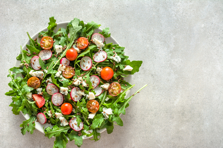Fresh salad with arugula and vegetables - feta cheese, tomato, seeds and radish. Organic vegetable diet, vegetarian food concept.