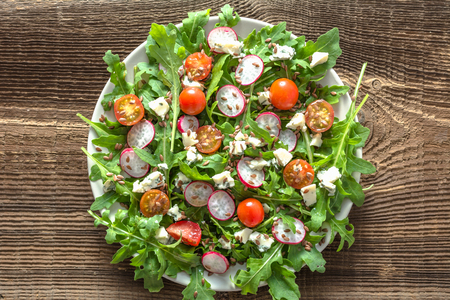 Healthy diet. Vegetable Fresh salad with arugula leaves, tomato, radish and seeds. Dietary appetizer or lunch on plate, vegetarian food concept.