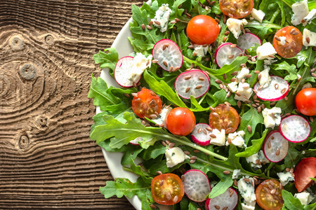 Fresh vegetable dish, salad with tomato, feta cheese and arugula leaves, healthy food concept