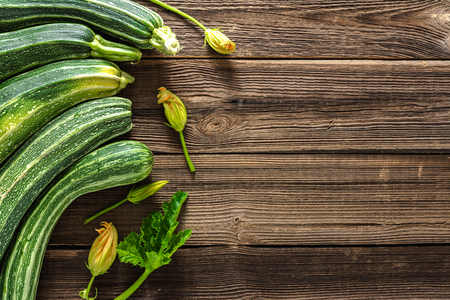 Fresh zucchini on wood. Organic vegetables on farmer market, courgette harvested in the summer. Imagens
