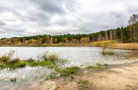 Cloudy autumn landscape with forest over lake Stock Photo