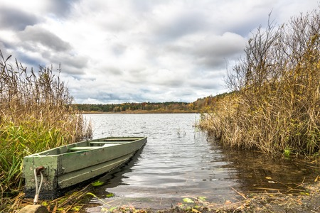 Fishing boat over lake, scenic landscape, autumn scenery with cloudy weather Stock Photo