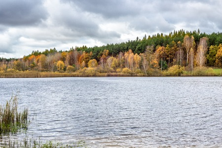 Autumn forest over lake, autumn scenery with colorful trees and cloudy sky Stock Photo