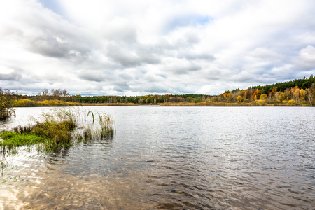 Cloudy autumn landscape with lake and forest Stock Photo - 107260182