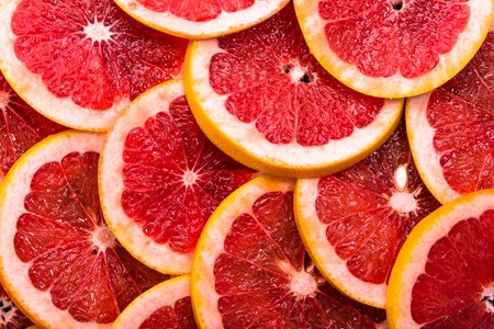 Sliced grapefruits, background, natural texture of citrus, top view, close-up Stockfoto