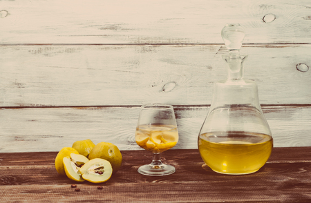 Glass of drink and carafe of alcohol tincture with quince fruits. Stock Photo