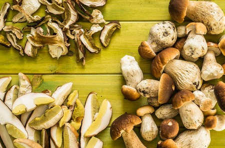 Fresh boletus mushrooms in a basket and dry mushroom on wooden table, overhead Stock Photo