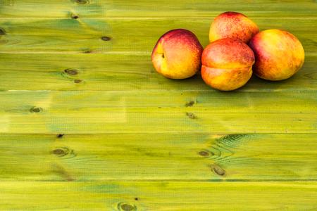 Ripe nectarine isolated on wooden background.