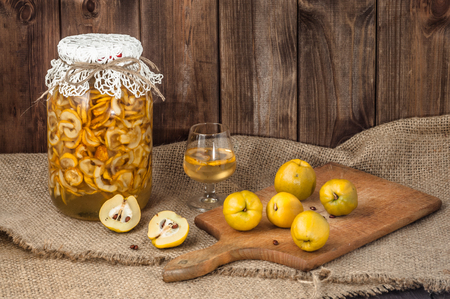 Quince tincture in a glass jar and fresh quince fruits on a wooden table