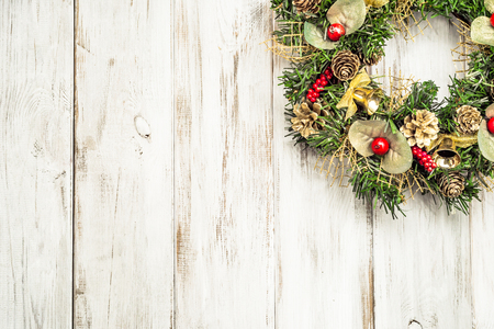 Christmas wreath hanging on wooden door, white background