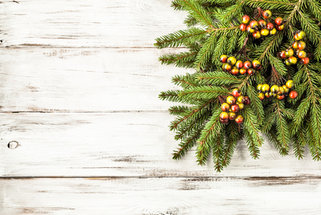 Green fir branch with christmas decoration on wooden white background Stock Photo
