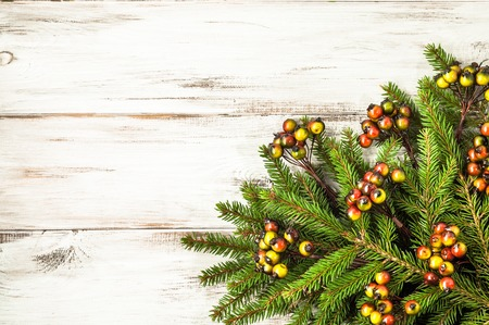 Green christmas fir branch with decoration on wooden white background
