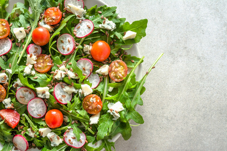 Healthy vegetable salad with fresh vegetables, vegetarian food on plate, top view