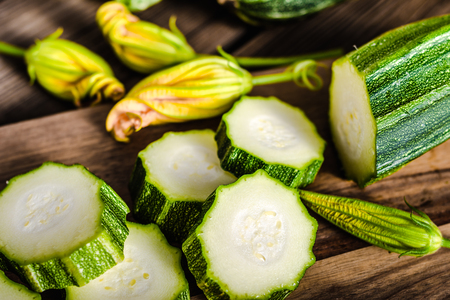 Fresh organic zucchini and slices, cooking food with vegetarian ingredients.