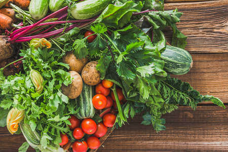 Farm fresh vegetable on wooden background, top view, vegetables and harvested produce from the garden