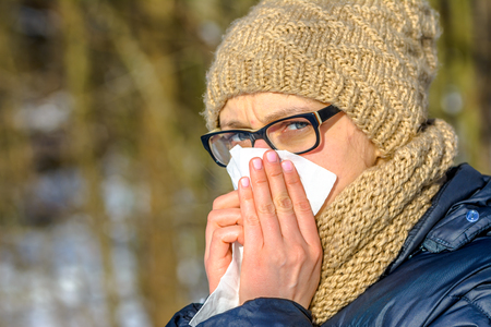 Sneezing woman blowing her nose with a tissue. Sick woman with cold and flu in winter, outdoors. Girl in warm clothes - hat and scarf Stock Photo