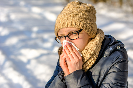 People with cold and flu. Woman blowing her nose with a tissue, outdoors Stock Photo