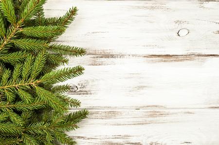 Rama de abeto verde sobre fondo blanco de madera Foto de archivo