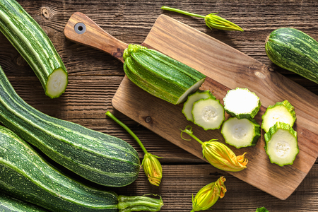 Fresh zucchini and slices of zucchinis on wooden table. Sliced courgette, healthy vegan diet or vegetarian food, cooking concept. Imagens