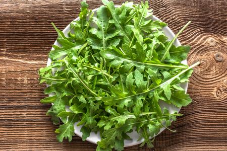 Fresh green leaves of arugula on plate, top view Reklamní fotografie