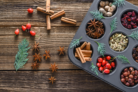 Decoration with christmas spice, background. Sweet spices for baking on wooden table - star anise, cinnamon stick, cardamom, nutmeg. Stock Photo